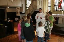 Bei der Predigt erkunden die Kinder ein kleines Ölgefäß mit Chrisam.